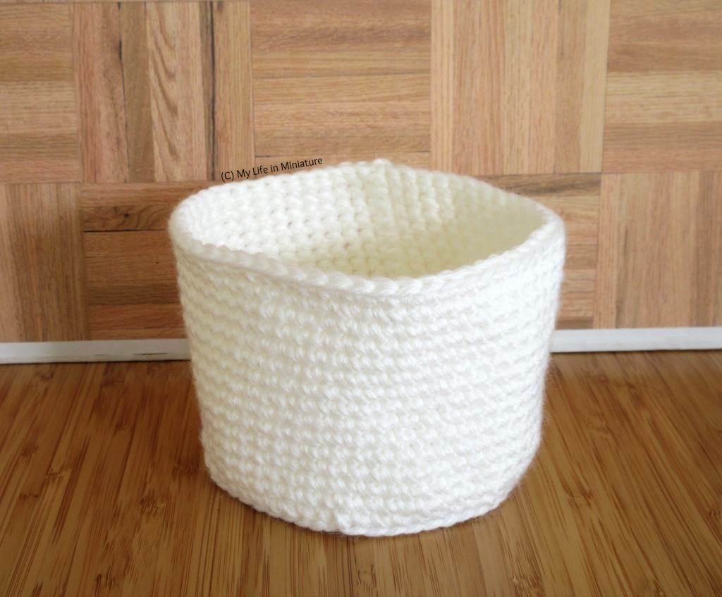 The completed white crocheted birds' nest sits against a wood background.