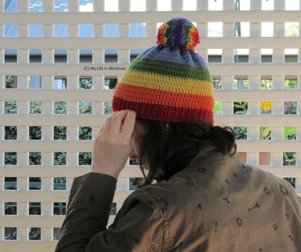 The author wears the rainbow beanie against a white lattice. Her head is turned almost fully to the left, but her face is blocked by her hand, which reaches up to adjust the ribbing.
