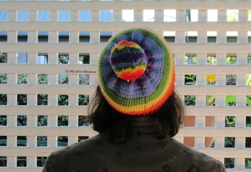 The author wears the rainbow beanie, back to the camera and against a white lattice. Her head is tilted back so the rainbow-striped pompom is visible from the top of the beanie.