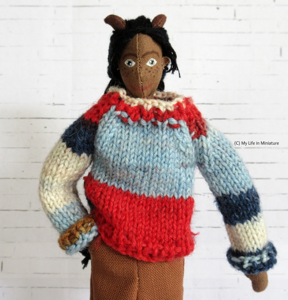 Petra wears a multi-coloured knitted jumper with brown pants. The jumper is red, pale blue, dark blue, white, and light brown. She has a hand in her pant pocket and smiles at the camera.