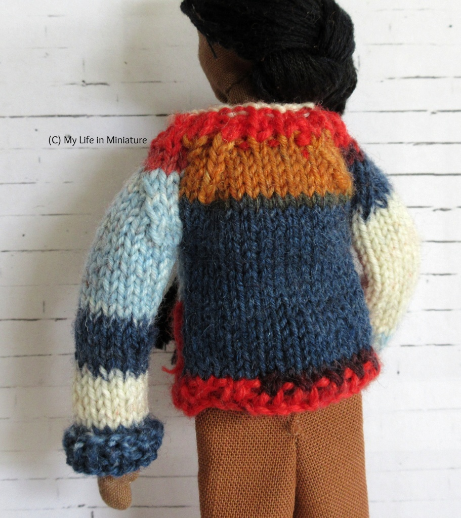 Petra has her back to the camera and her hair over her shoulder, showing the back panel of the multi-coloured jumper. The back panel is red, dark blue, and light brown.