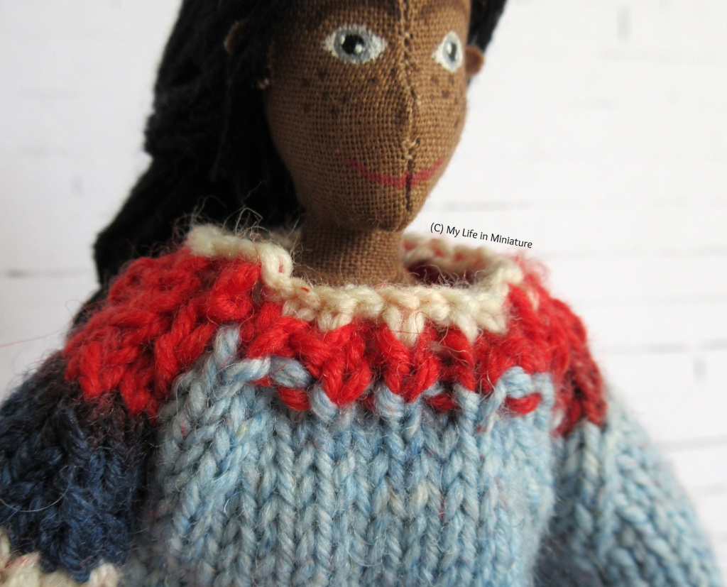 Close-up of the neckline of Petra's multi-coloured jumper. It is red and white knit ribbing, and sits just below her neck.