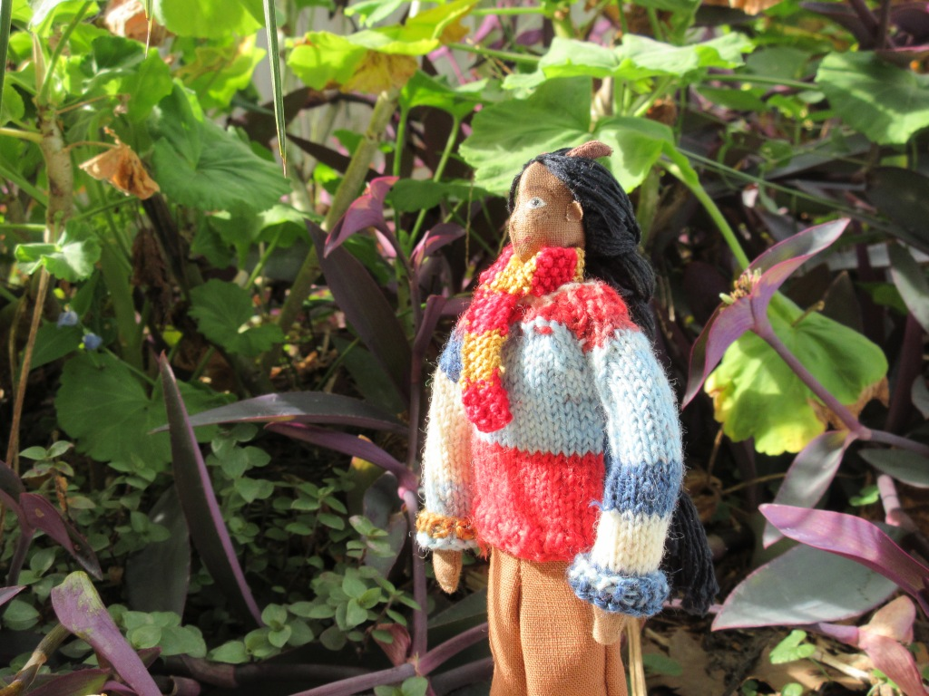 Petra stands outside in amongst leafy plants in green and purple. She looks up at the plants, face half-shaded by a leaf. She wears her multi-coloured jumper with the sleeves turned up, brown pants, and a red-and-gold knitted scarf.