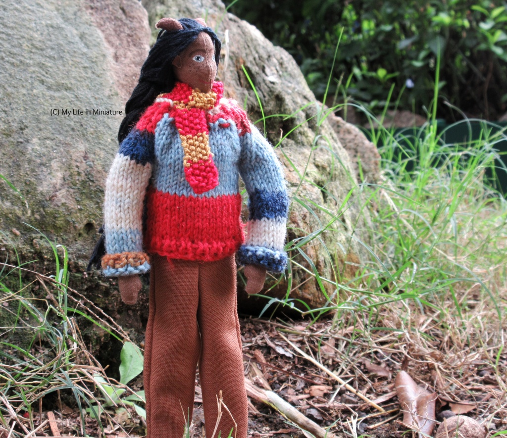 Petra stands outside, in front of a rock. Beside the rock is some tall green grass and some leaf litter. Petra wears the multi-coloured jumper with the sleeves turned up, brown pants, and a red-and-gold scarf. She looks to the right, smiling softly.