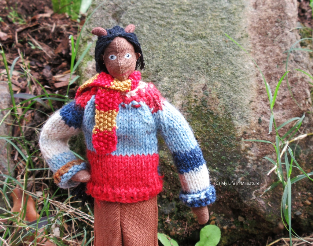 Petra stands outside, in front of a slightly green-ish rock. She wears the multi-coloured jumper with the sleeves turned up, brown pants, and a red-and-gold scarf. She has a hand on her hip, and smiles at the camera.