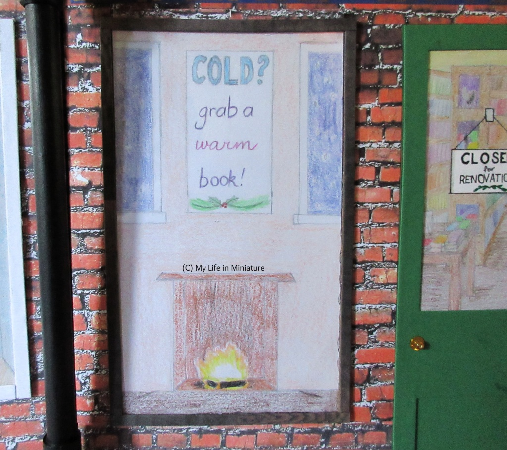 The front window of The Palace Library is visible. A wintery display is in the window, depicting a small scene around a fireplace. Above the fireplace (in which a fire burns) is a piece of 'art' that says 'Cold? Grab a warm book!'. Part of a window to a dark blue snowy exterior is visible on each side of the artwork.