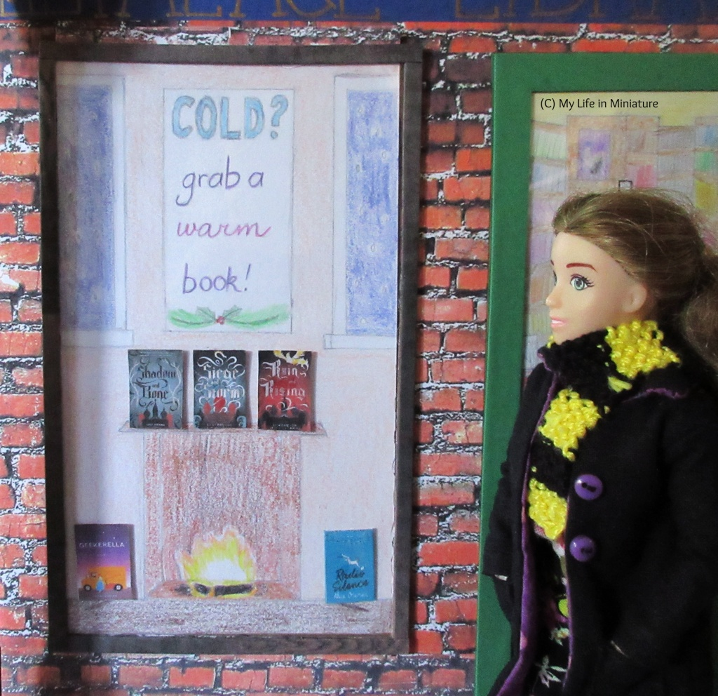 Sarah stands beside The Palace Library's front window, looking at it. The window has the wintery display with a fireplace and the text 'Cold? Grab a warm book!' above it. Three books sit on the mantlepiece of the fireplace, and two more are on the floor on either side of the fire.