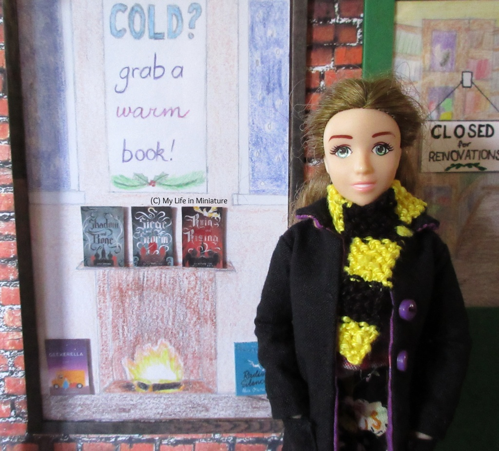 Sarah stands beside The Palace Library's front window, which has a wintery display inside. She smiles at the camera, hands tucked into her coat pockets, and scarf wrapped around her neck.