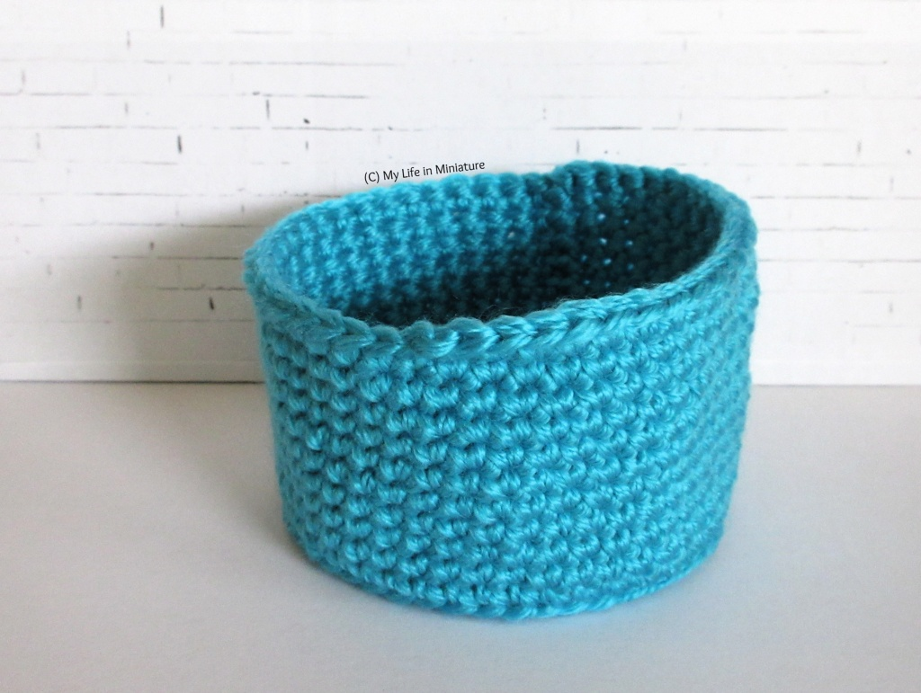 A blue crocheted birds' nest sits against a white brick background.