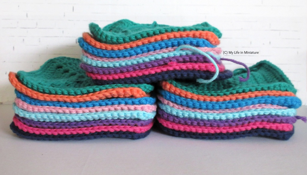 Three stacks of crocheted squares, eight squares high, sit against a white brick background. One stack of eight sits on top of the other two stacks, like a small pyramid.