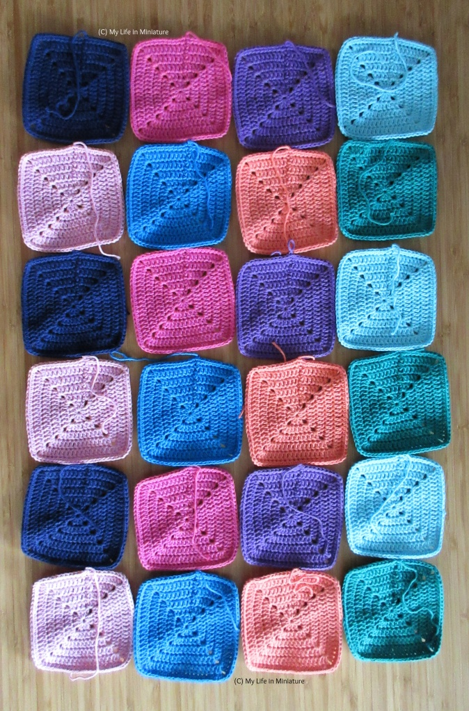 All 24 crocheted squares are laid out in a long rectangle, four by six squares. They are laid out in colour order - navy, pink, purple, pale blue, pale pink, blue, peach, and green.