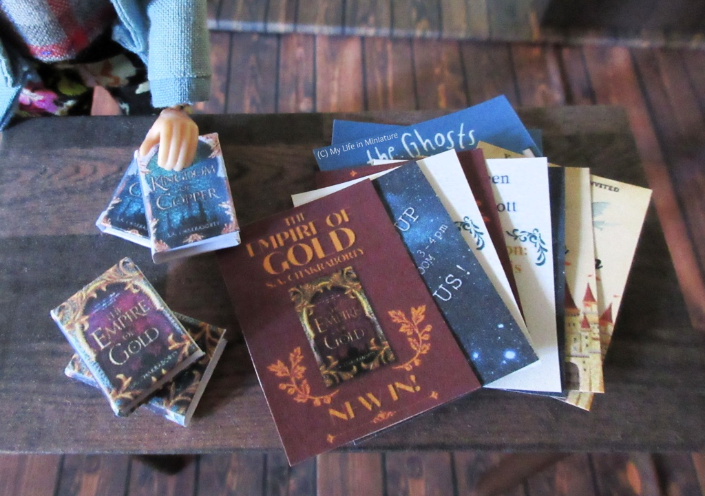 Four books and a stack of papers sit on a small dark wood table in The Palace Library. Sarah's hand rests on one of the books, which are stacked in two stacks of two. The papers are all various promotional flyers for various things: new books, author talks, fan groups, and the like.