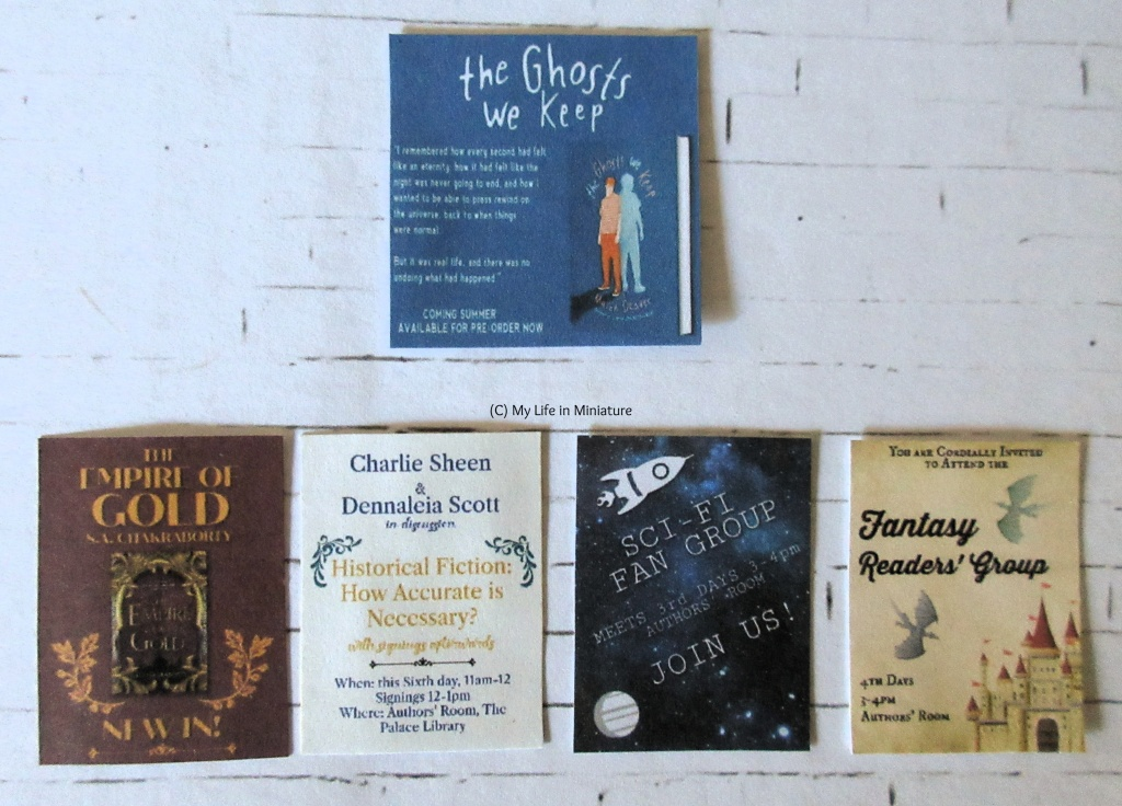 The five different flyers sit flat on a white brick background. They are arranged in a row of four at the bottom, and one at the top centre. The top centre one advertises a book called 'The Ghosts We Keep'. The bottom row advertises, left-right; a book called 'The Empire of Gold', two authors in discussion about 'Historical Fiction: How Accurate is Necessary?', a sci-fi fan group, and a fantasy readers' group.