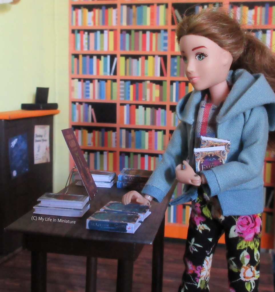 Sarah stands at the small wooden table in The Palace Library. She has a few books in her arm, and is placing one of them on the table. Six or so books are already arranged on the table around a wire bookstand with a flyer resting on it.