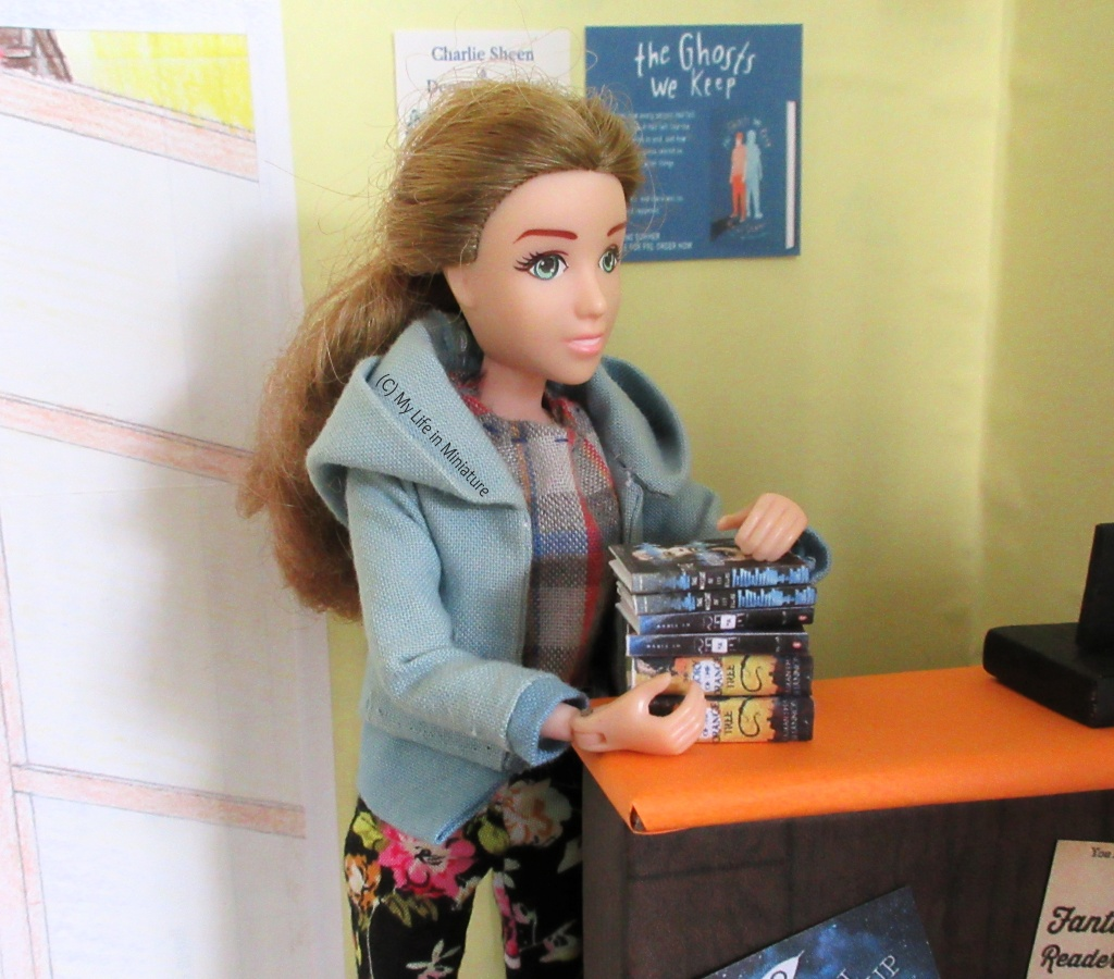 Sarah eases the stacked six books off the Palace Library's counter and into her arms. She looks down at the books, and is wearing a blue hoodie and floral pants.