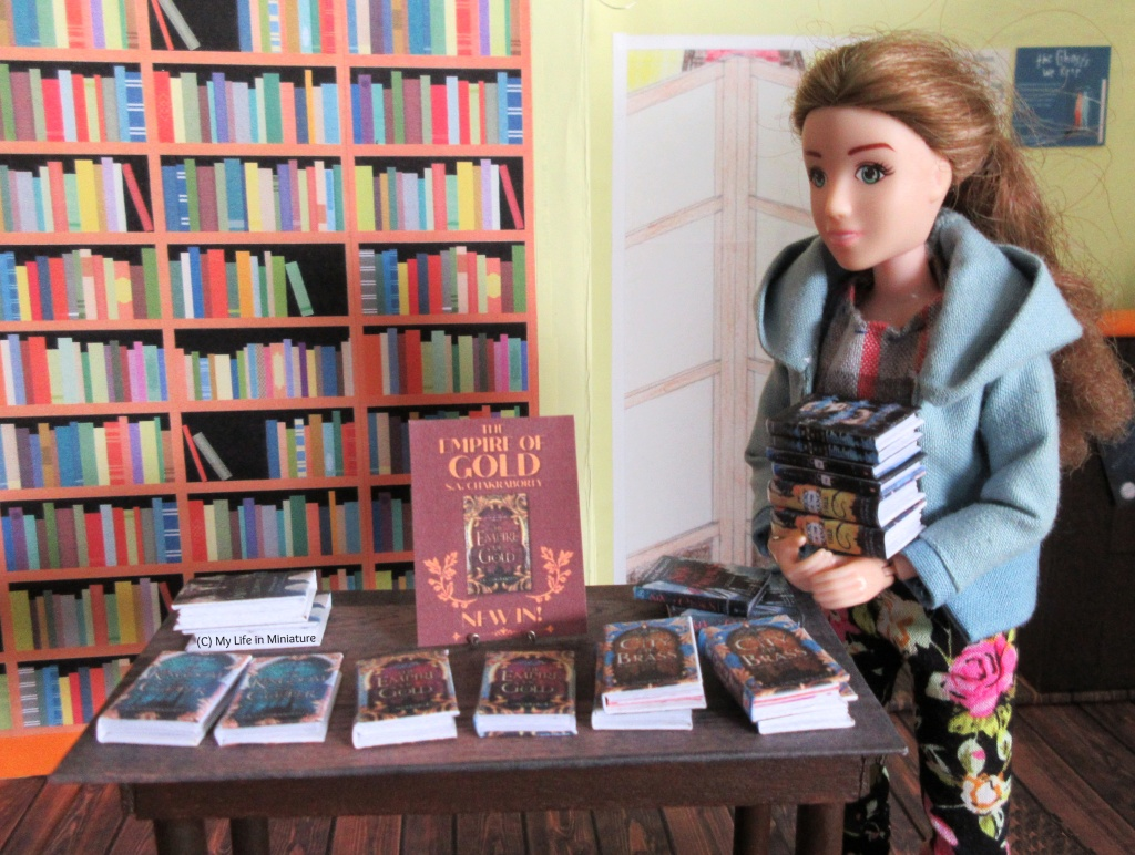 Sarah carries the stack of six books in her arms, standing near the small free-standing wooden table in the Palace Library. The table has a variety of books on it, and a red flyer that advertises a 'new in!' book called 'The Empire of Gold'. Sarah looks at the table, thinking.
