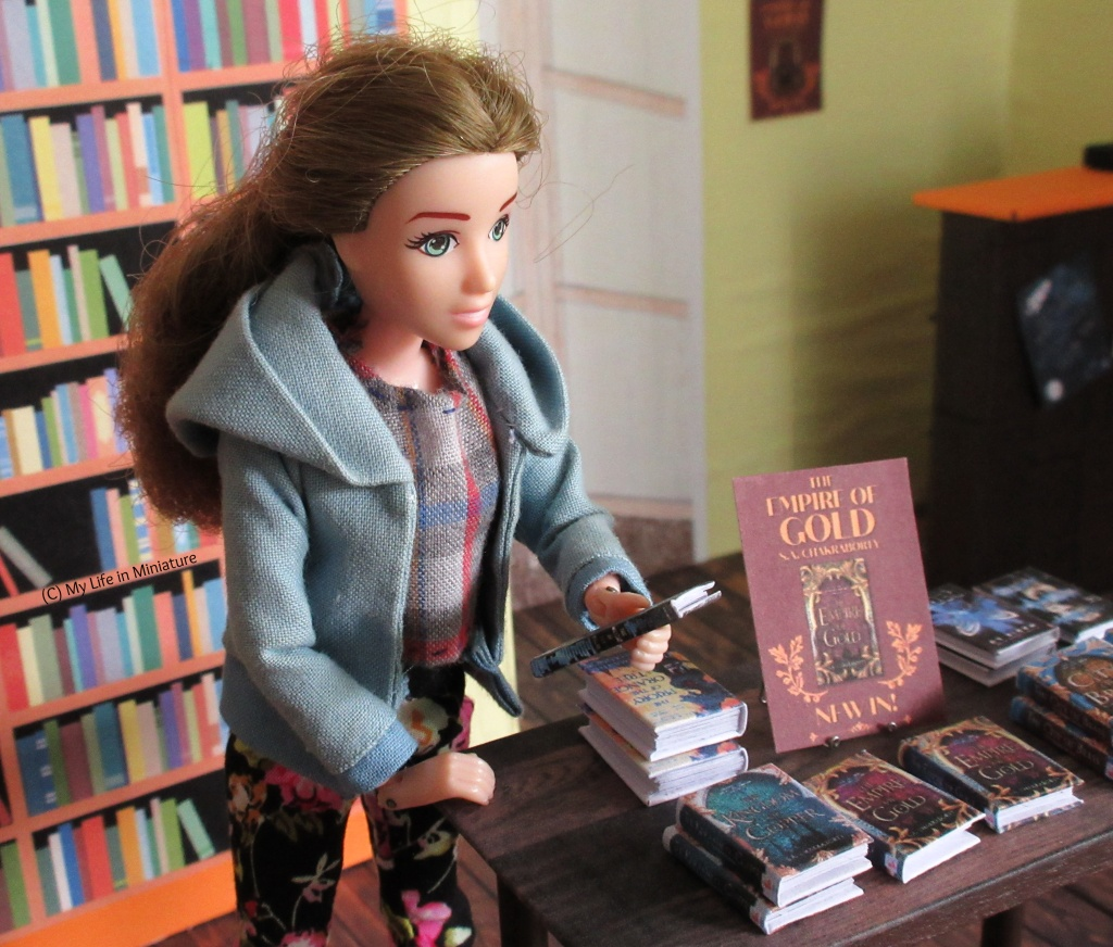 Sarah stands at a corner of the free-standing table in the Palace Library, wearing a blue hoodie and floral pants. She is looking at a book she's holding, called 'The Weight of the Stars', reading the blurb with interest.