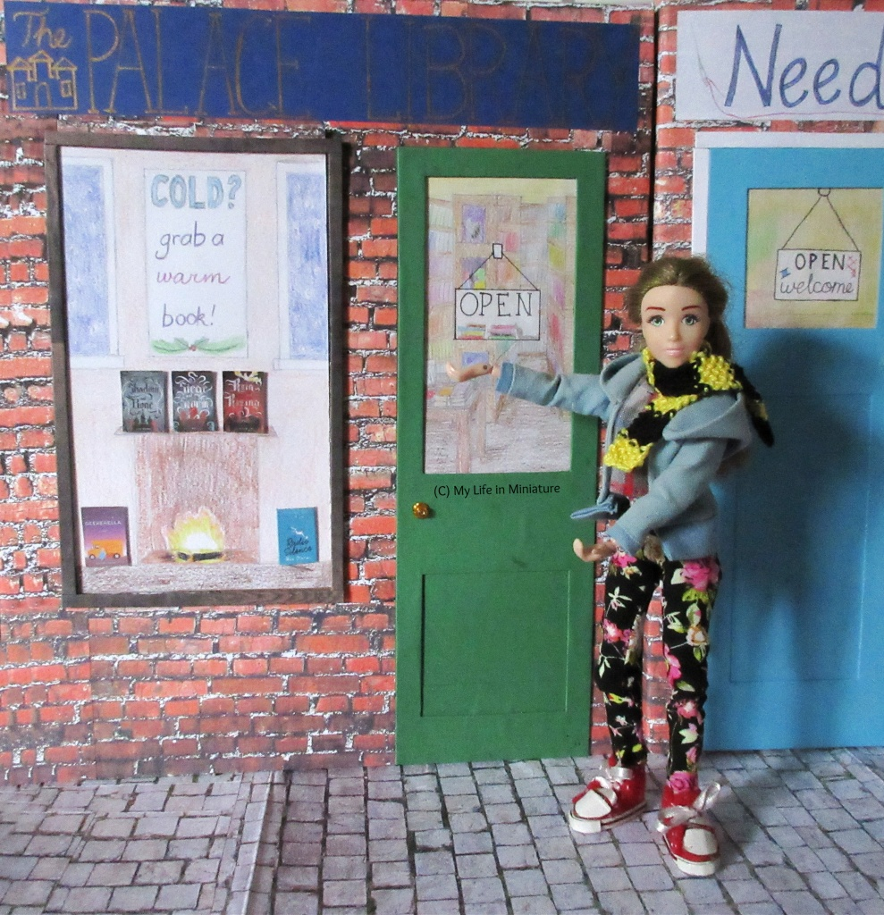 Sarah stands outside the Palace Library, gesturing dramatically at the façade. She wears a blue hoodie, black floral pants and a knitted scarf. The Palace Library has a green door, a blue-and-gold sign, and a window display that says 'Cold? Grab a warm book!'.