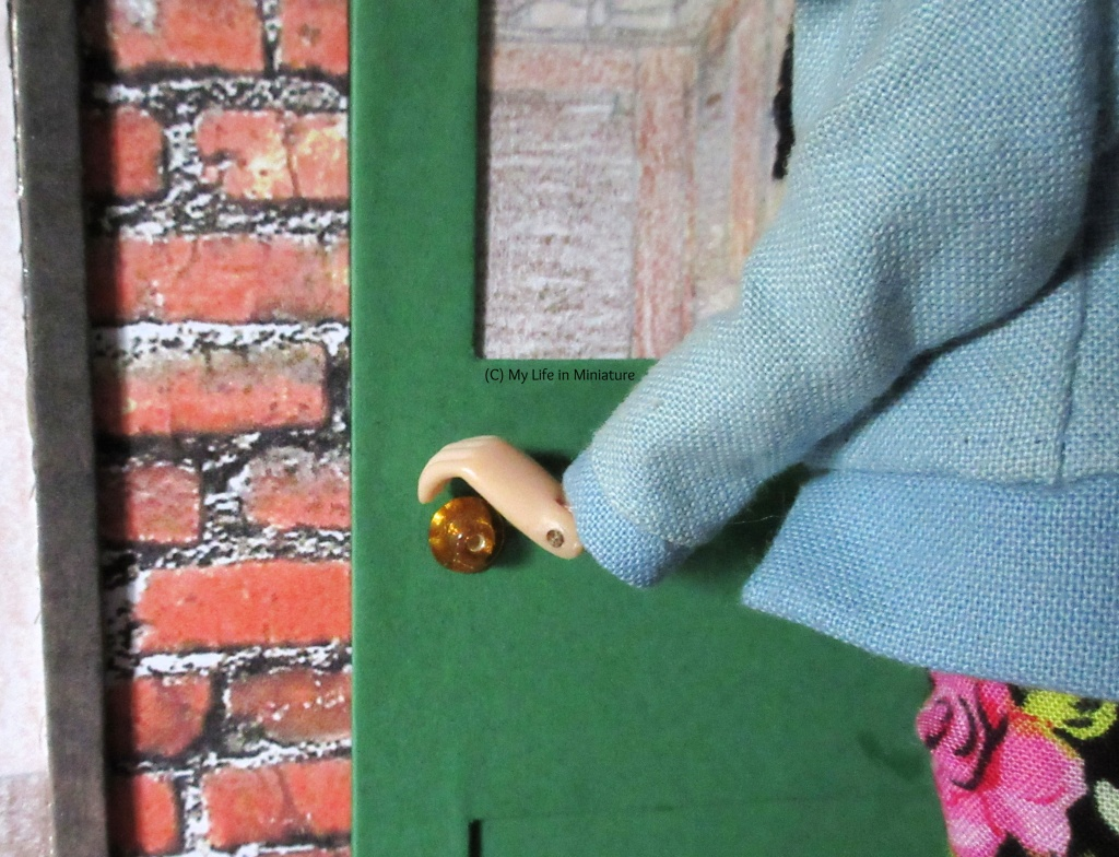 Close-up of Sarah's hand as it grasps the gold doorknob of the Palace Library's front door.