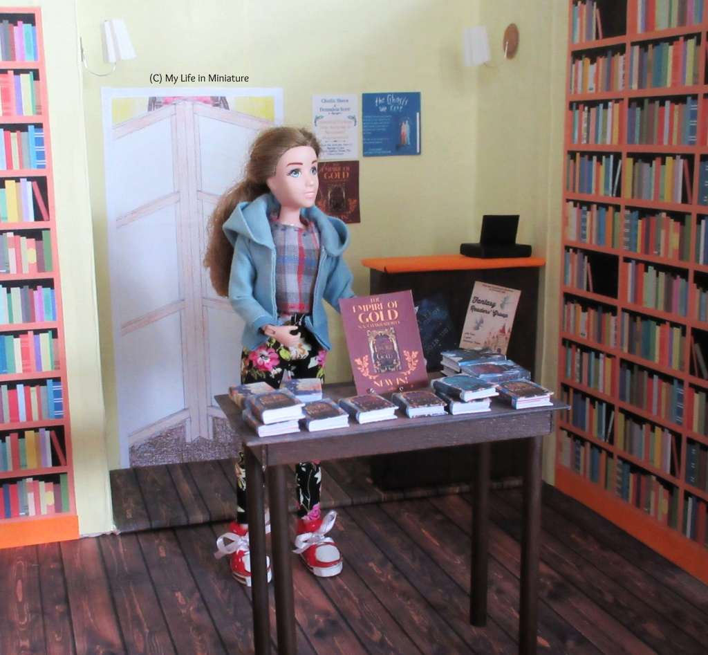 Sarah stands in the centre of the counter area, display table in front of her. She gestures around to the space, and looks to the right. The display table has several stacks of books on it, with a flyer advertising one of them on a wire book stand. A counter is in the background, as well as a doorway blocked by a room divider and bookshelves.