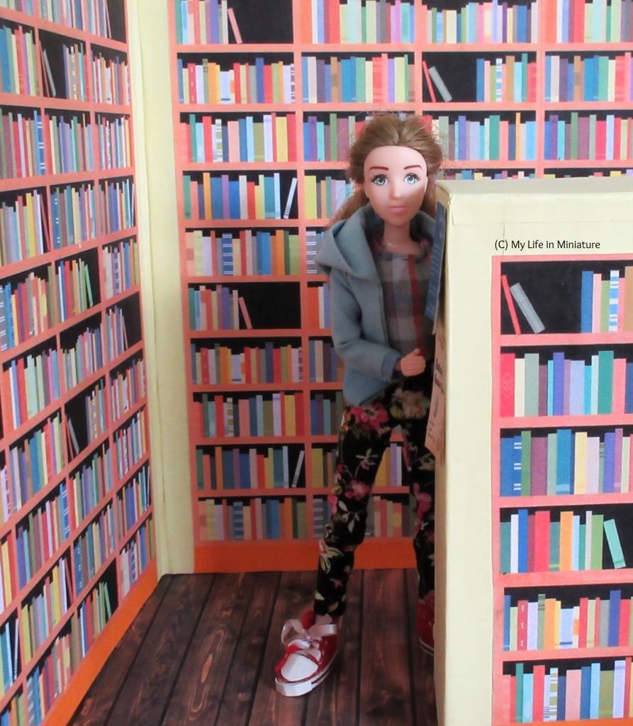 Sarah leans out from behind the end of an aisle in the Palace Library. She is surrounded on all sides by bookshelves full of books. Some flyers are on the end of the aisle, which goes up to about Sarah's eyes in height.