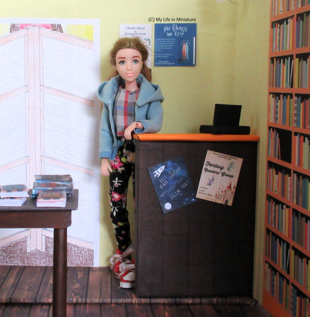 Sarah stands behind the counter at the Palace Library. She rests an elbow on the counter, and smiles into the camera. On the wall behind her are more flyers, mostly blocked by her hair. A corner of the display table is visible in the foreground.