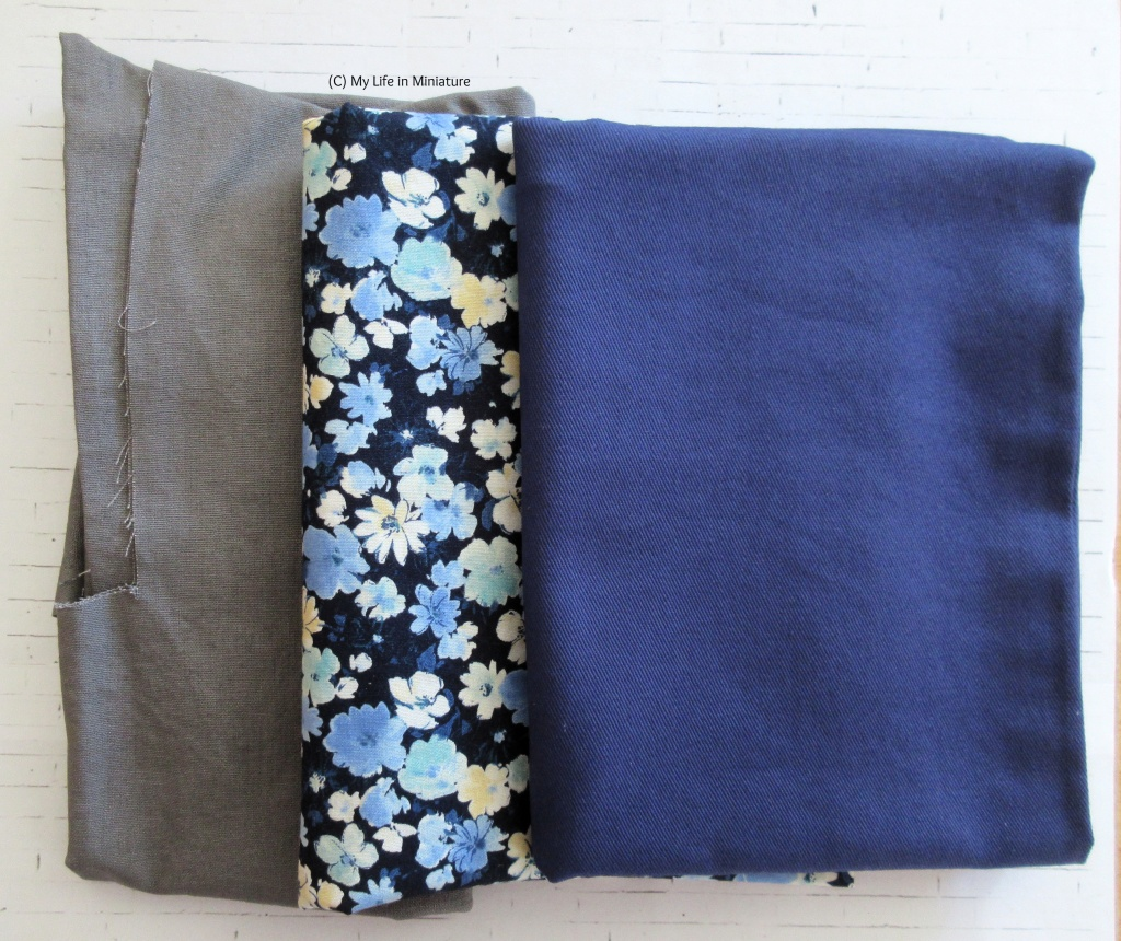 Three folded-up pieces of fabric sit on a white brick background. They are stacked in a staggered manner, so they are all visible. Left-right, there is a grey cotton that has clearly been used, a dark blue cotton printed with pale blue, white, and yellow flowers, and a heavier dark blue fabric.