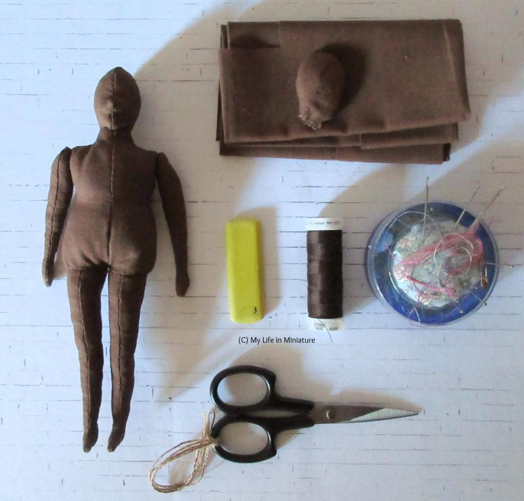 A hand-sewn doll body, along with various tools used to make it (including fabric, scissors, thread, needles, and tailor's chalk) sit on a white brick background. The fabric - and the doll - are dark brown.