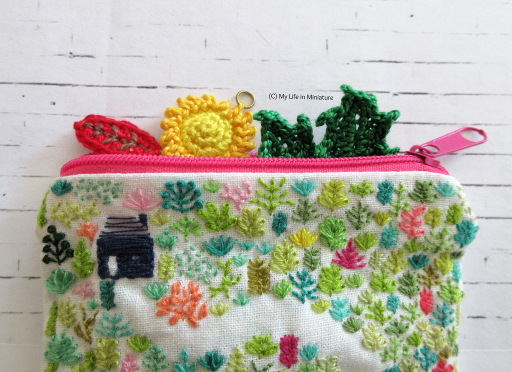 An embroidered zipper pouch sits, open, on a white brick background. Peeking out the opening at the top of the bag is a small crocheted red leaf, sun, and green leaves.