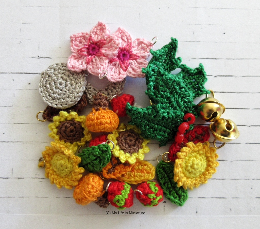 A pile of small crocheted objects is on a white brick background. The objects all have a jump ring on them, and are mostly crocheted natural objects - apart from two gold bells on the right of the pile.