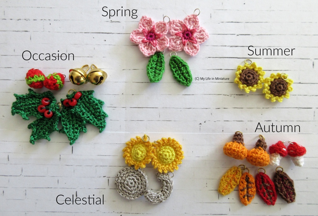 22 crocheted objects (and two gold bells) sit on a white brick background, arranged into five categories. Clockwise from the top is spring, summer, autumn, celestial, and occasion. The spring category has two green leaves, and two cherry blossom flowers. The summer category has two sunflowers. The autumn category has two pumpkins, two red-topped mushrooms, and four leaves in shades of yellow, orange, red, and brown. The celestial category has two suns, and a full and crescent moon in silver. The occasion category has the two gold bells, two baubles, and two bunches of holly.