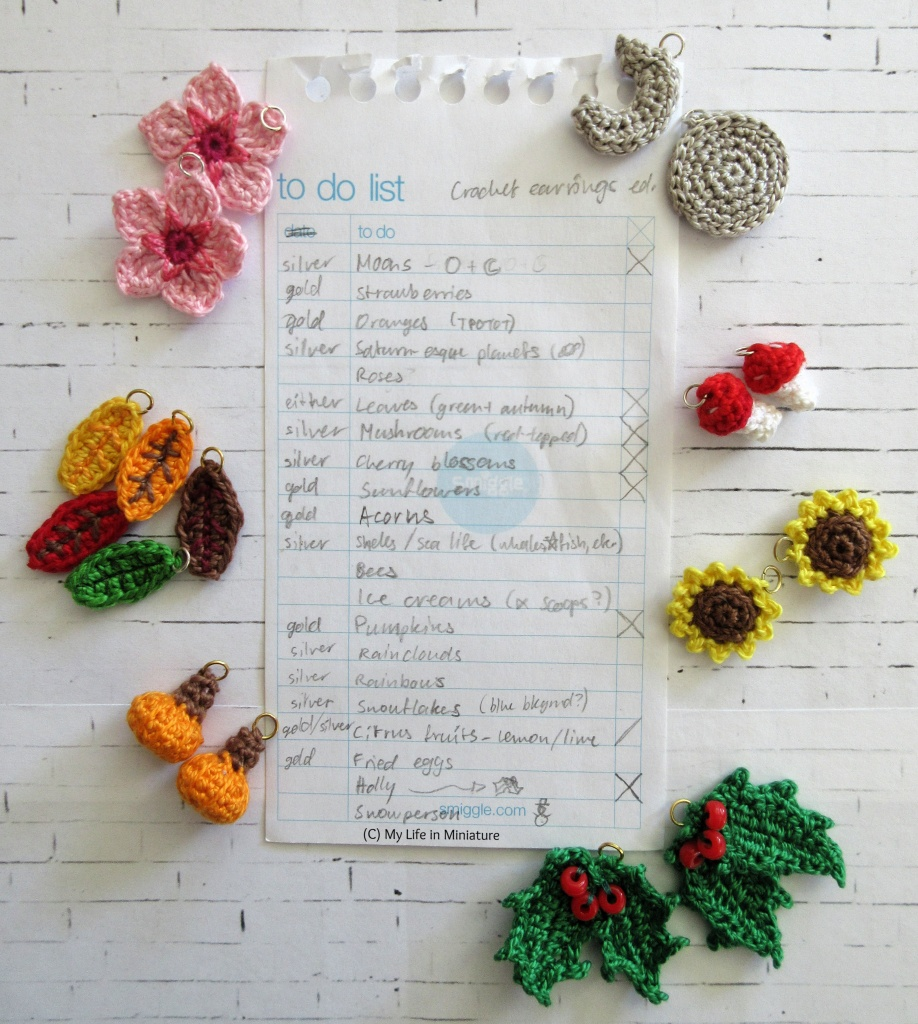A hand-written list is surrounded by various small crocheted objects, on a white brick background. The list is titled 'To Do List: Crochet Earrings Edition'. Several of the items are crossed off, and the completed earrings sit roughly beside the list. The completed items include sunflowers, mushrooms, moons, cherry blossoms, autumn leaves, pumpkins, and holly.