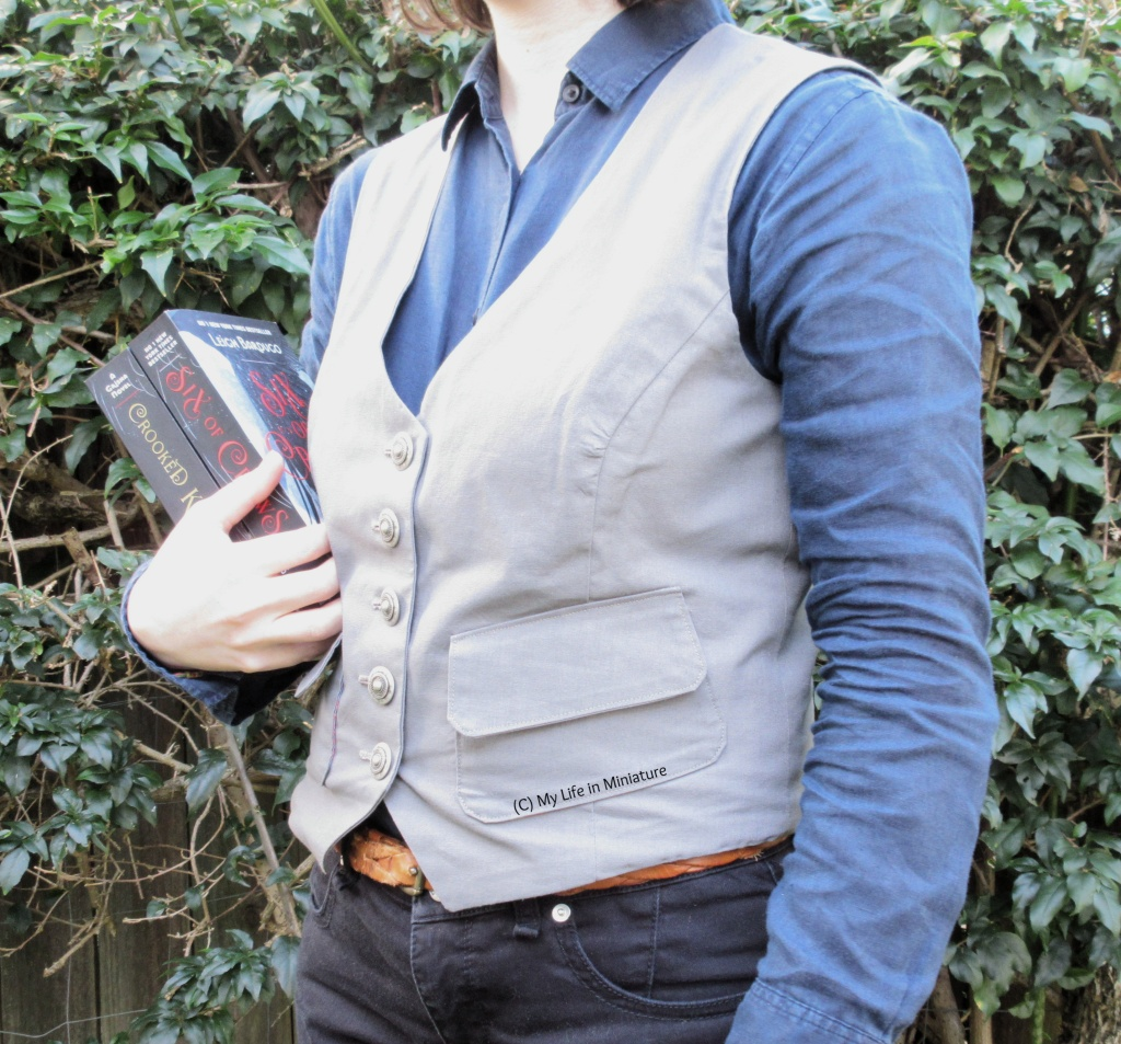 The author stands in front of a hedge, wearing a grey waistcoat, a navy button-up shirt, and black jeans. She carries the Six of Crows duology by Leigh Bardugo. She is white with shoulder-length brown hair, just visible on the collar of the shirt.
