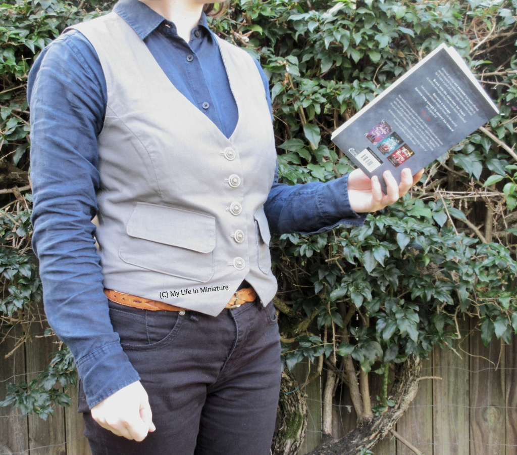 The author stands in front of a hedge, wearing a grey waistcoat, a navy button-up shirt, and black jeans. The waistcoat has two small pockets on the front, with flaps over the openings. She holds the book 'Six of Crows' by Leigh Bardugo in her right hand, open as if reading it. Her body is angled to the right of the image.