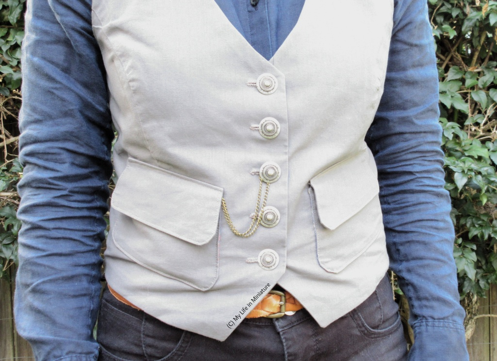 The author stands in front of a hedge, wearing a grey waistcoat, a navy button-up shirt, and black jeans. From the left pocket emerges a chain, which loops over the centre button and hangs loosely.