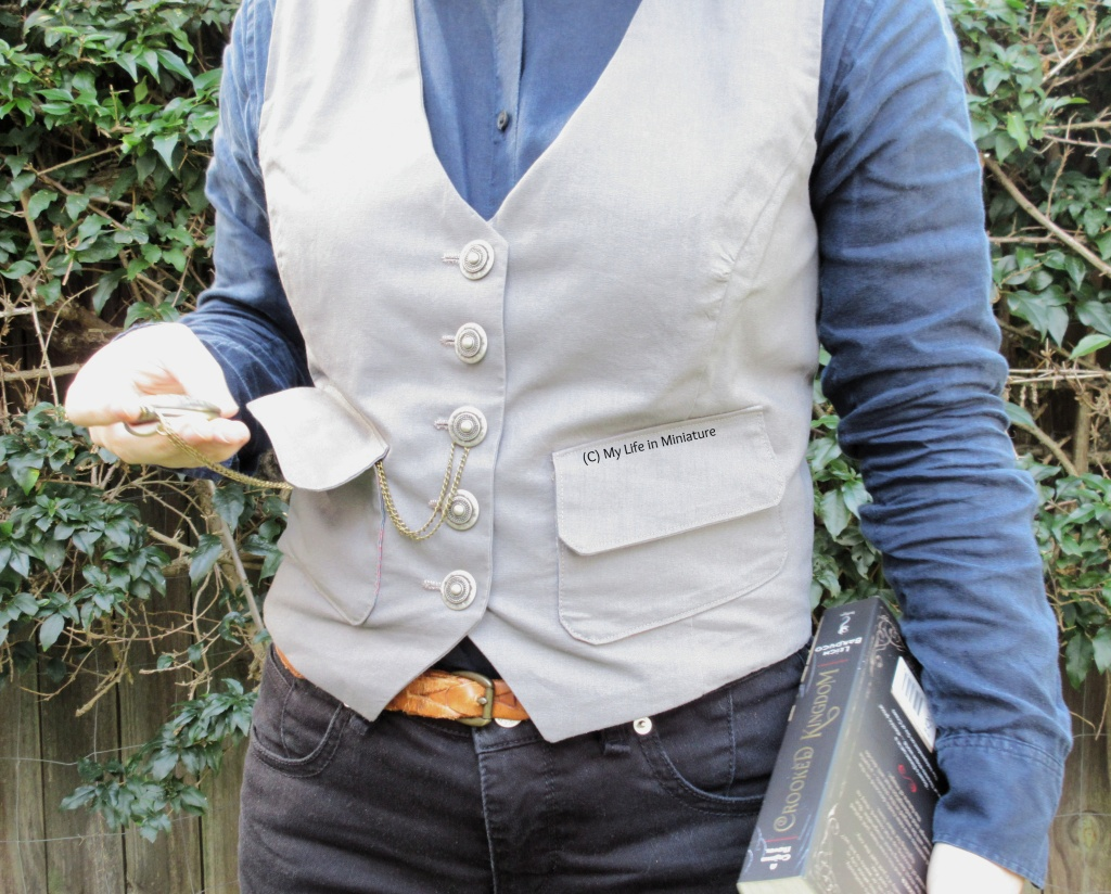 The author stands in front of a hedge, wearing a grey waistcoat, a navy button-up shirt, and black jeans. She holds 'Crooked Kingdom' by Leigh Bardugo in her right hand, and a pocket watch on a chain in her left.