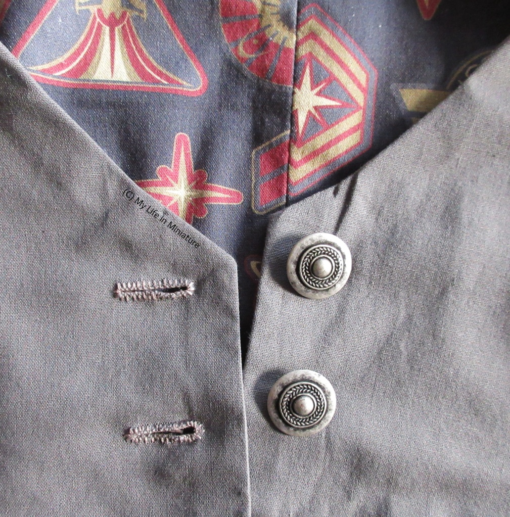 Close-up of the centre front of the grey waistcoat. The top two buttons are visible, as well as the top two hand-bound buttonholes. The buttons are tarnished silver, round, and have a leafy pattern around the centre. The lining is also visible behind the fabric panels.