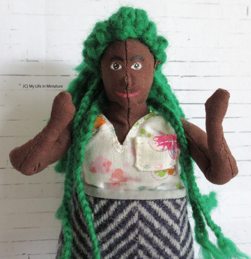 Hazel looks at the camera, grinning and waving. She is black and fat, with dark brown eyes and bright green hair in braids. She wears a white v-necked top with pink flowers on, and a chevron-print wool skirt.