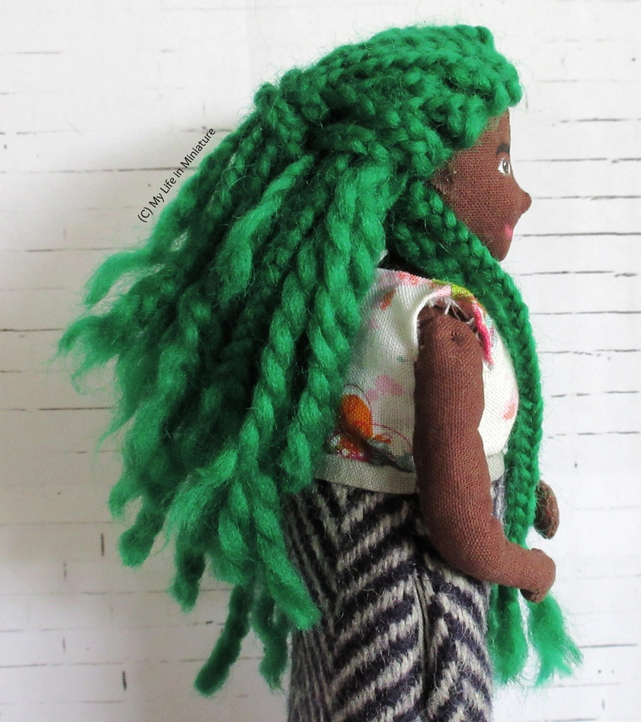 Hazel faces towards the right of the image, so her face is in profile. Her bright green hair is the subject - some of it is braided, and some of it is wound like yarn. A lot of the braids are gathered in a half-up style, with some pushed over her shoulder. The length varies, with the longest strands reaching past her hips.