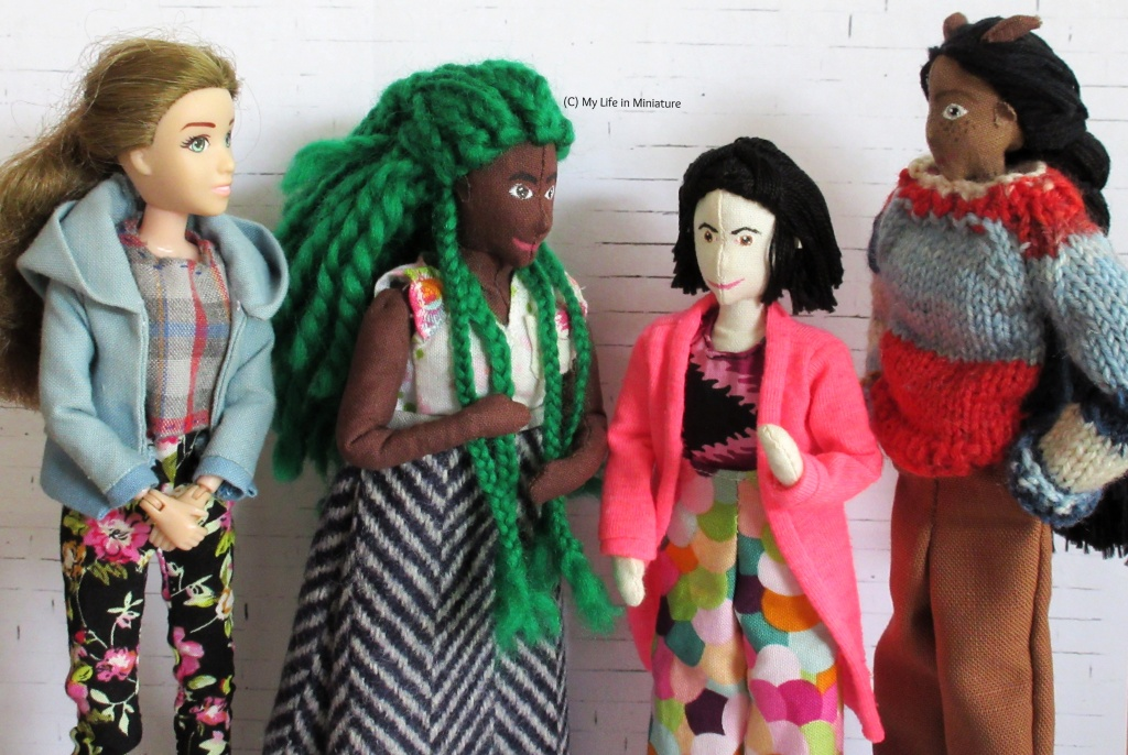 Sarah, Hazel, Tiffany, and Petra stand left-right against a white brick background. They all look at Tiffany, who is gesturing in speech. Hazel fiddles with her braids, Sarah's hands are clasped in front of her, and Petra has her hands in her pockets. Sarah wears a blue hoodie, a checked shirt, and black floral pants. Tiffany wears a bright pink cardigan, black and purple shirt, and multi-coloured scalloped pants. Petra wears a red and blue jumper and brown pants.