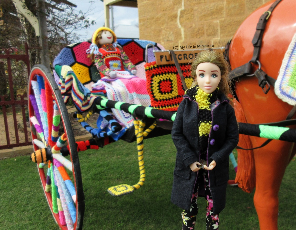 Sarah stands in front of a small carriage that has a big plastic horse hitched to it. The horse's behind is visible, though most of the background is filled with the carriage. The carriage sits two people, and is covered in crochet - the seat, the wheel spokes, the little step to get into it. A larger doll sits in the carriage.