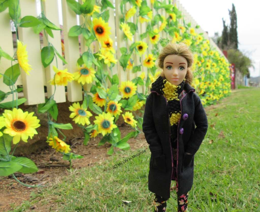 Sarah stands on grass near a cream-coloured fence, which has been covered with plastic sunflower vines. The fence extends into the background behind Sarah. She wears a knee-length black coat with a black-and-yellow striped scarf, and has her hands in her pockets, smiling at the camera.