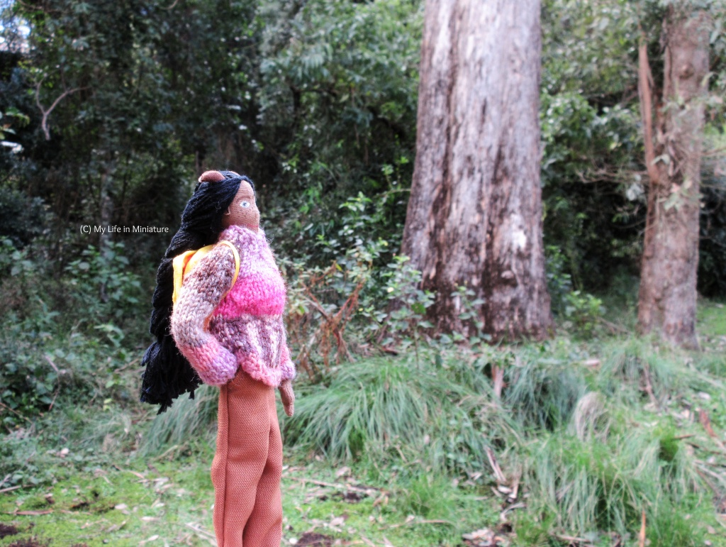 Petra stands near the base of a tree trunk, facing right, head tipped back to try and see the treetop. She wears a pink-and-purple jumper with brown pants, and has her yellow backpack on. She has her closest arm in her pant pocket.