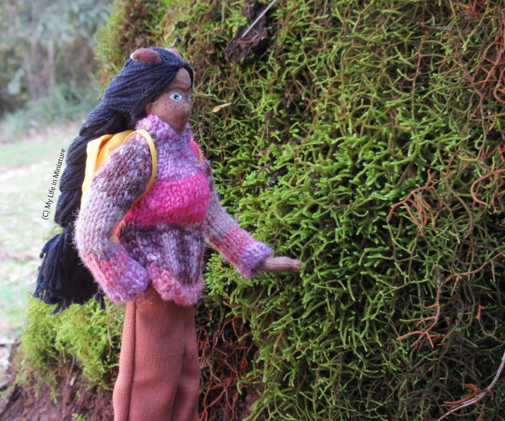 Petra stands very close to the base of a tree trunk, gently stroking some moss growing on it.