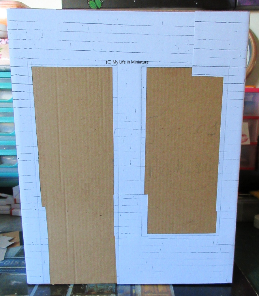 The front of a cereal box fills the image, covered in cardboard that peeks out from behind white brick paper. Two roughly rectangular holes are left in the paper for a door and a window, which the cardboard is visible through.