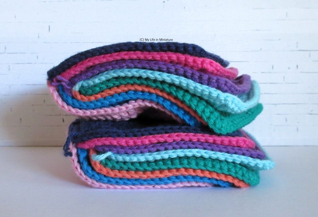 A stack of crocheted squares sits against a white brick background. The squares are sewn together in pairs along one edge, then stacked and folded in half. Two separate folded stacks of squares are stacked in the image.