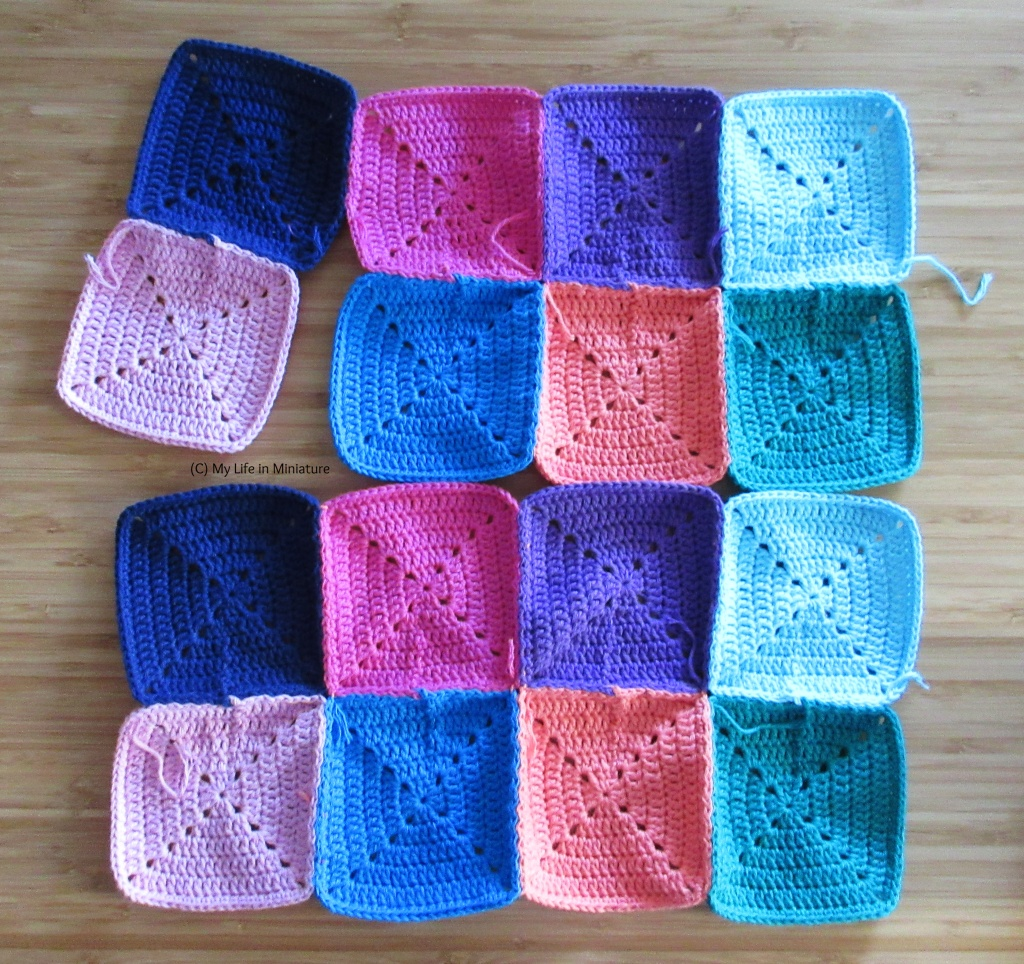Two rectangles of crocheted squares are flat on a wooden background. Both rectangles are 2 by 4 squares; the bottom rectangle is completely sewn together, and the top one has two squares on the left partially connected to the rest.