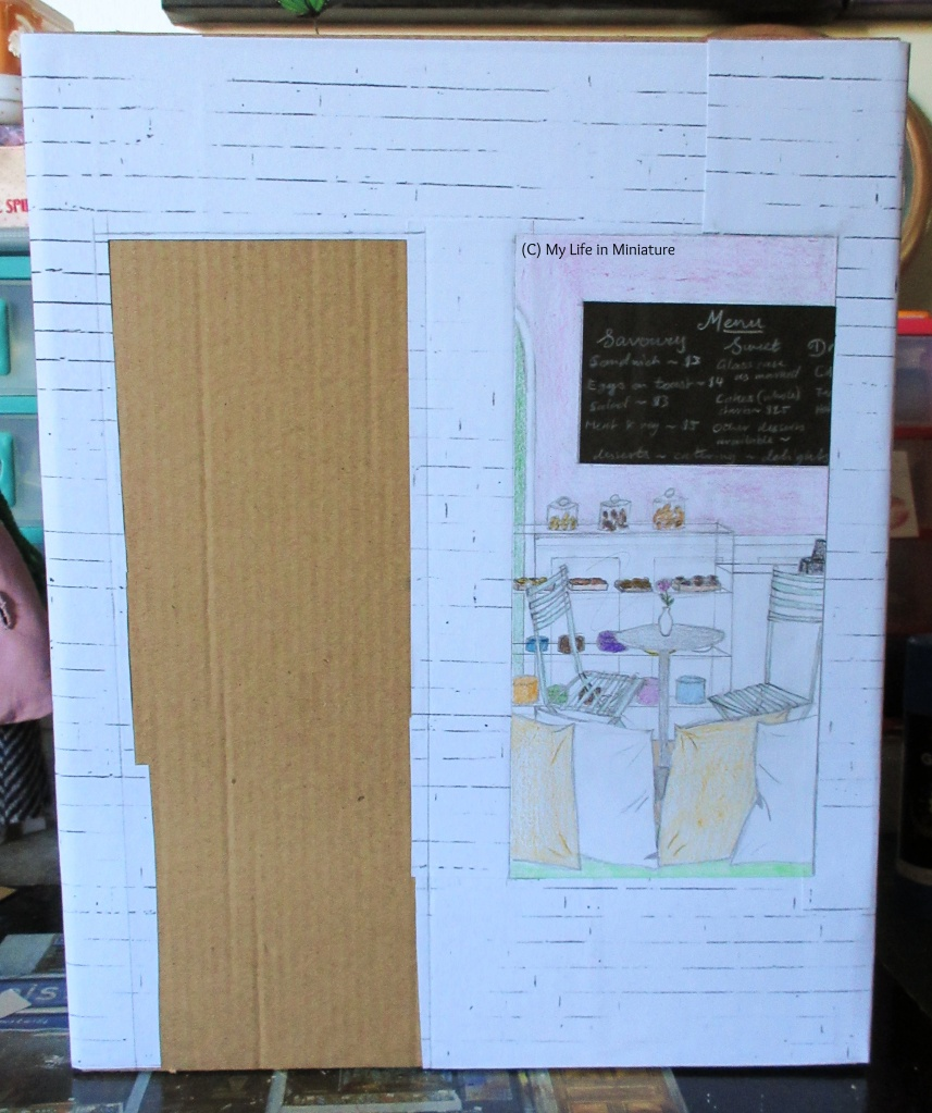 The front of a cereal box fills the image, covered in cardboard that peeks out from behind white brick paper. A rectangle for the door is left uncovered on the left of the box, and a view into the shop is on the right. 'Inside' the shop is cushions on a window seat in the foreground, a table and chairs in the midground, and a counter filled with desserts in the background. On the wall in the very back is a chalkboard menu.