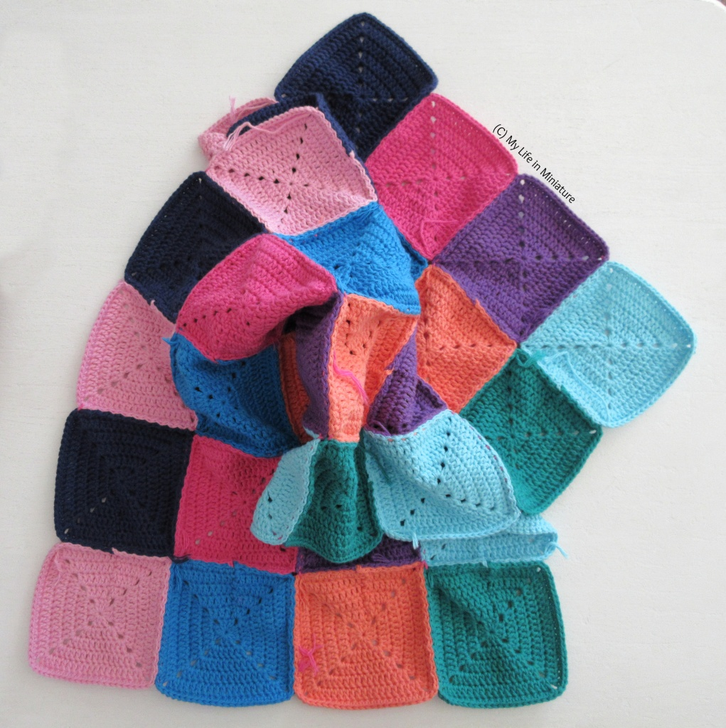 32 crocheted squares, of various colours, are sewn together to make a long rectangle of fabric. This rectangle is curled and scrunched up in the centre, so the entire length of the rectangle is not visible. It is on a white background.