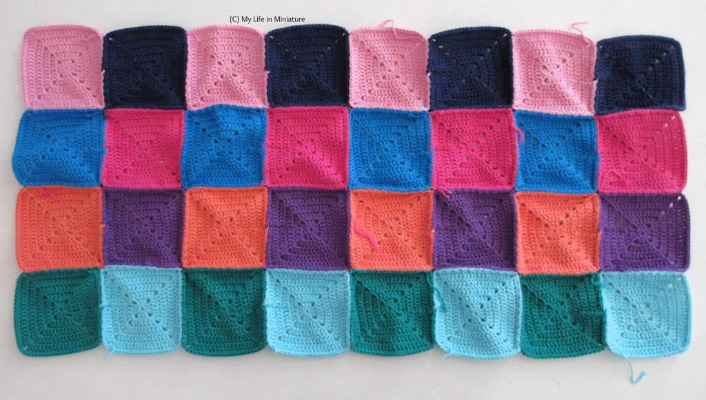 32 crocheted squares, of various colours, are sewn together to make a long rectangle of fabric. It sits on a white background. A few loose ends are visible around the edges of the rectangle.